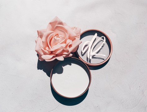 image of a rose next to an open tin of the Deux Rosé Beauty Refinery Makeup Brush Soap.